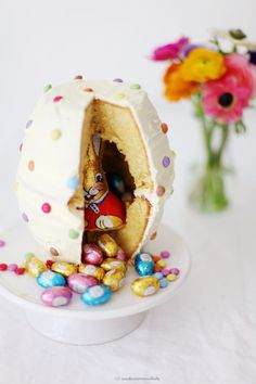 Easter egg themed pinata cake with easter bunny and chocolate eggs hiding image